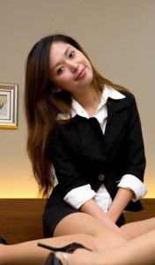 A nice secretary sits on the ground, posing for a picture. She wears a professional but attractive black outfit.